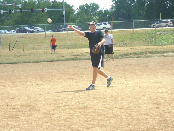 At the junction of Highway 63 and 34, Andy Pearson pitches during a game Sunday for an Ottumwa adult softball league. Temperatuers stayed in the mid- to upper-80s. <br /> Mark Newman/The Courier