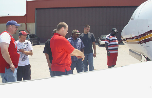 "Aviation instructor Dan Brauhn describes both an air brake and a possible secret exit for commandos to Indian Hills avionics and maintenance students on a ""walk-around"" inspection of a jet Tuesday. Temperatures were in the mid-90s."