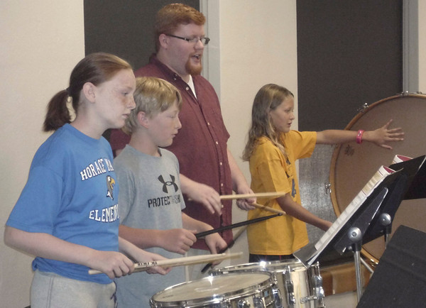 Assistant summer band director Aaron Schuck works with future fifth-graders Macy Duff, Hunter Gullion and Katie Nelson in the band room Thursday at Evans Middle School.<br /> Mark