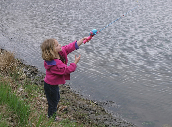 Olivia, 5, casts her line Saturday at Ottumwa Park. Grandpa says she can handle a bigger fishing pole, but he thought a smaller model would be better at the crowded fishing derby. <br /> Mark Newman/The Courier.