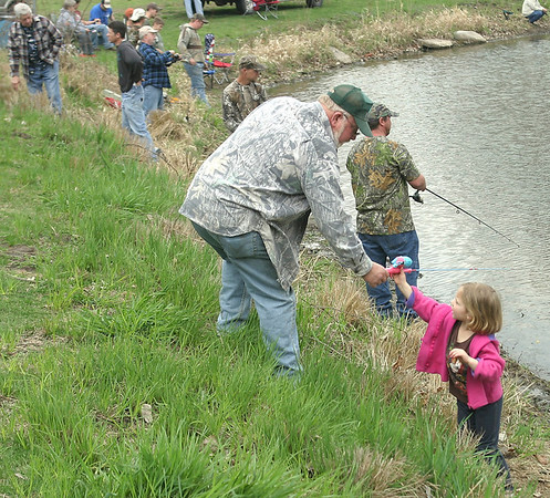 Mark Newman/The Courier<br /> Grandpa Kenny Archer, Ottumwa, hands Olivia Ann Harris, 5, her fishing pole Saturday at the annual fishing derby. Officials believe more than 200 people showed up.