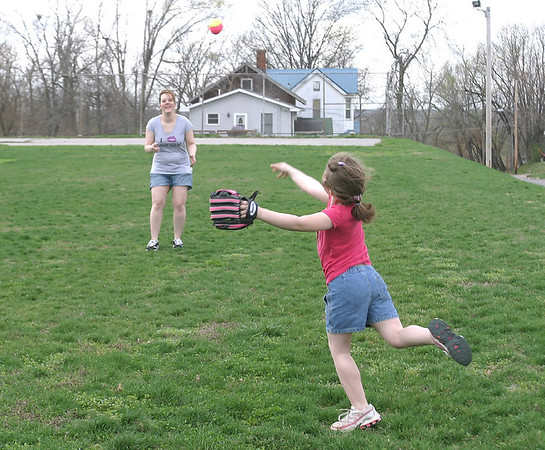 Mom Shana Wasko of Ottumwa plays catch with daughter Zoie, 6, after the weather cleared Tuesday afternoon. The National Weather Service says there's a chance of rain every day this week.