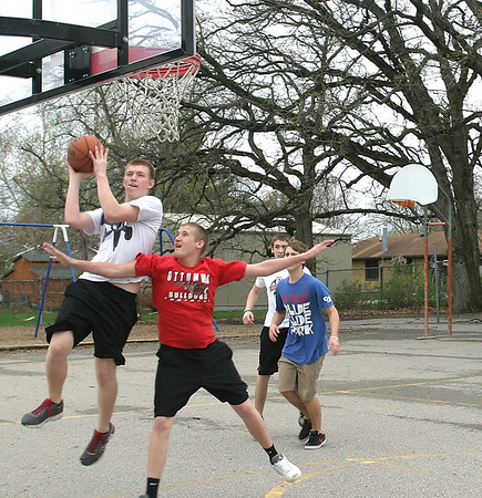 Avery Palen, an Ottumwa student on spring break, goes up for a shot while being blocked by Brandon Zeitler while shooting hoops Wednesday with Jesse Millard and Reuben Palmer.