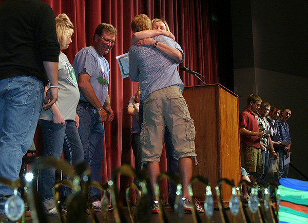 The Anderson family presents scholorships in memory of their son Seth to Ottumwa High School students Tuesday. One of many special moments at the Senior Honors Assembly included the presentation of a scholorship — and hugs — to family friend Zach Messer.