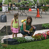 Mya Sampson, 4, helps her mom, Tiara Formaro of Ottumwa choose something to pretty up their yard Saturday during the annual Laureate Guild Plant Sale. The sale this year was held in Central Park.