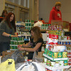 Students, including Lilly Throgmartin, left front, and Lois Ivey, were happily drafted Monday to help sort thousands of pounds of food collected by OHS students and staff. The food will go to restock the shelves at the Southern Iowa Food Bank.