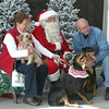 Carol and Carl Anderson of Ottumwa convince Molly, Dora and Diego to relax and sit still for their picture with Santa. The Santa Paws benefit Sunday at Earl May helps raise funds for the Heartland Humane Society — where the Andersons adopted all three of their dogs.