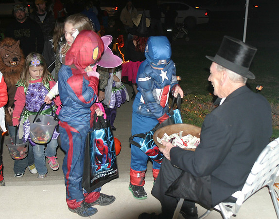 Doug Robertson, right, watches as Spider-Man struggles to choose which candy to take during Halloween Wednesday night in Ottumwa. A nearby resident said she expected up to a thousand trick or treaters.
