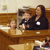 Shari Bowman of Fairfield gets some help answering the judge's questions from son Hayden, 4 and daughter Hailey, 2 while at the Wapello County Courthouse Saturday during adoption proceedings.