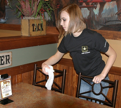 Army Strong<br /> Mark Newman/The Courier<br /> Chasity Music of Chariton clears off a table Friday at Pizza Ranch in Ottumwa during Tip Night for the Wounded Warrior Project. Music ships out for U.S. Army boot camp this winter.