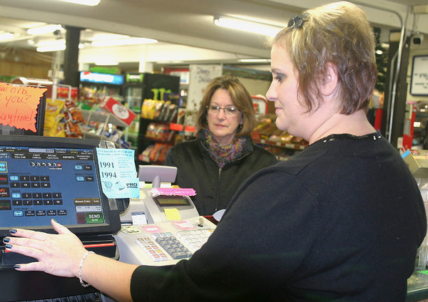"""Quick Shop manager Sara Johnson sells a Powerball ticket to Lora Myers of Ottumwa. In addition to a ticket purchase Tuesday, the Ottumwa resident is also in a """"pool"""" at work."""