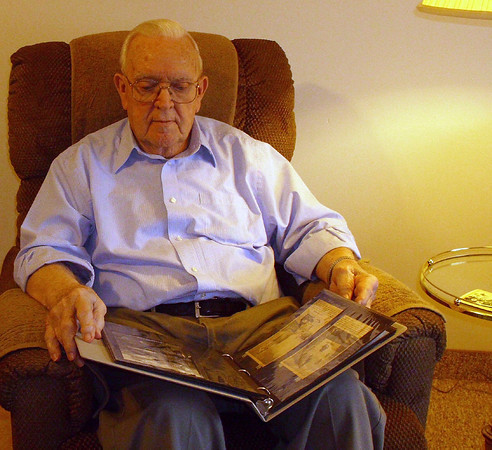 Neil Harriss of Ottumwa flips through a book of memories he created for his sons. Harriss served in England during WW II.