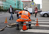 An employee of OAO Moscow City Telephone (MGTS) sits on an upturned traffic cone while working beside a manhole cover in the middle of a city street in Moscow, Russia, on Tuesday, Sept. 10, 2013. The ruble gained for a fifth day as Chinese economic data improved and a Russian proposal for Syria to surrender its chemical weapons eased concern over a U.S. strike, boosting investor appetite for riskier assets. Photographer: Andrey Rudakov/Bloomberg