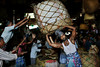Indian laborers drop a large heavy bundle of vegetables in front of a vendors stall at a wholesale vegetable market in Kolkata, eastern India, Wednesday, April 17, 2013. (AP Photo/Kevin Frayer)