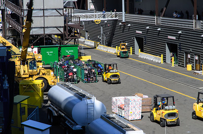 The loading area at Pier 91 in Seattle, WA. You can see the green luggage containers are full of passenger bags, and also boxes of food and even a large bag of onions. At the top of the picture you can see the gangway where passengers are boarding the ship. A steady stream of people boarded all afternoon.