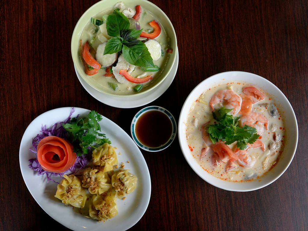 . Thai dumping appetizer, bottom left, green curry with chicken, and shrimp curry, from Phuket Thai Restaurant in Louisville. Cliff Grassmick  Photographer November 1, 2017