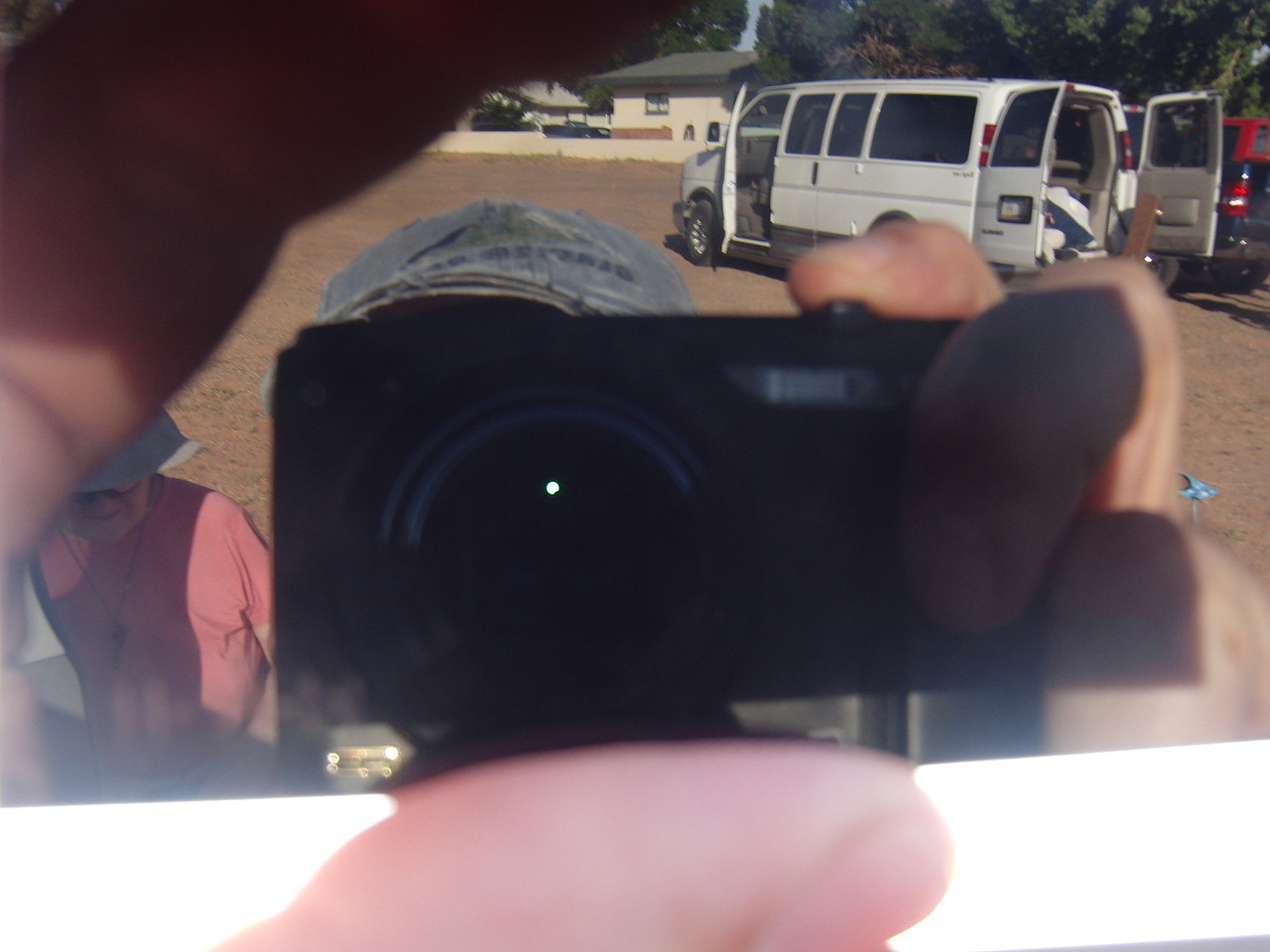 Dr. Winslow takes a picture through the welding glasses.  The next photo shows a closeup of the apparition.  Notice the camera, Dr. Young, and the school van in the reflection of the glass.  The Sun is on the other side of the glasses.