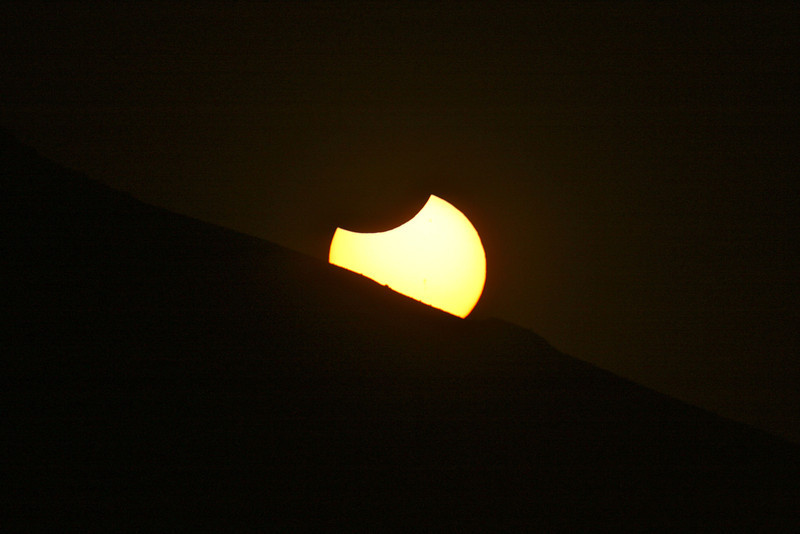 The moon is not quite out of the sun when it is setting at Page, AZ.  Here, you see the Sun being eclipsed by the moon and the Earth simultaneously.