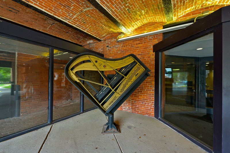 This grand piano on its side marks our main entrance on Spring Street. Our two parking lots are close by. So is trash disposal.