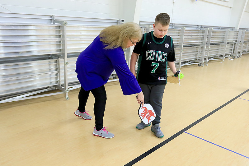 Kids at the Boys and girls club of Fitchburg and Leominster learned about the game of pickleball from some volunteers that love to play. Volunteer Ginni Bilodeau helps Tyler Strong, 11, from Leominster learn the game. SENTINEL & ENTERPISE/JOHN LOVE