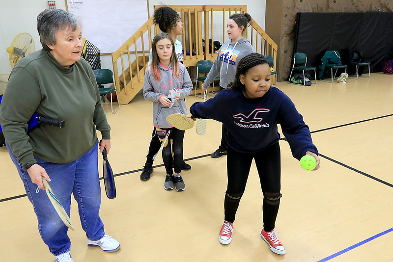 Kids at the Boys and girls club of Fitchburg and Leominster learned about the game of pickleball from some volunteers that love to play. Volunteer Helen Bradford watches Hasel Mutindawa, 12, of Leominster serve the ball as she teaches her the game. SENTINEL & ENTERPISE/JOHN LOVE
