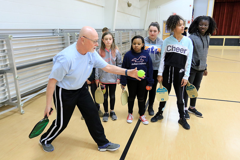 Kids at the Boys and girls club of Fitchburg and Leominster learned about the game of pickleball from some volunteers that love to play. Volunteer Richard Meehan teaches some of the kids how to serve as he teaches them the game. SENTINEL & ENTERPISE/JOHN LOVE