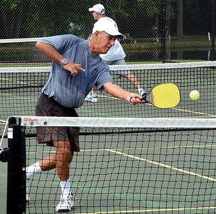 Mike Goodman follows through at the net in pickleball matchup at Masons Mill Park in Huntington Valley. (John Gleeson – 21st-Century Media)