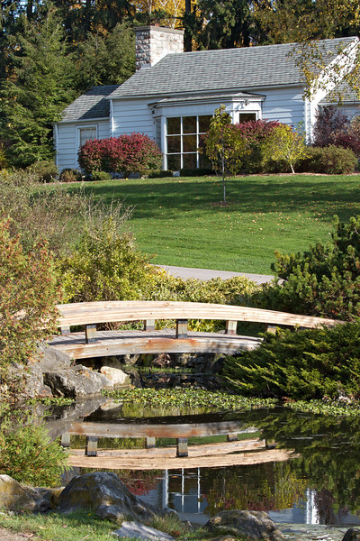 Beautiful home landscaping with footbridge over pond