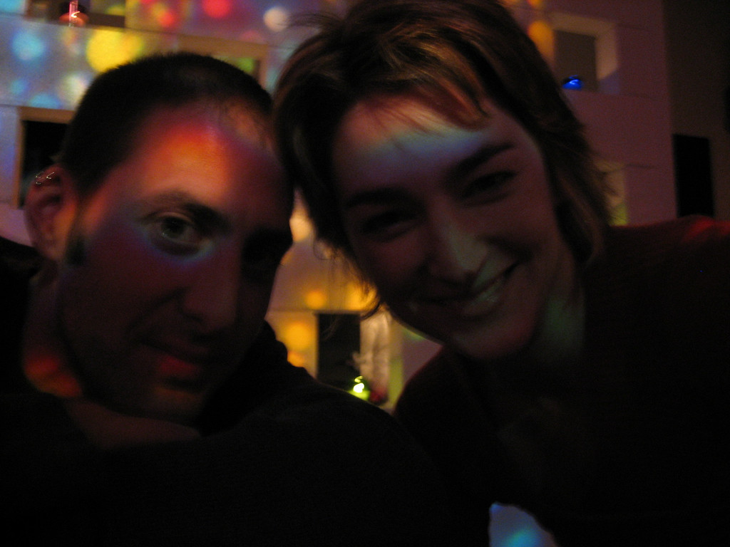 """MARCH 16, 2006<br /> <br /> Joe Schmelzer and me at Vinyl on 9th Avenue. We were surrounded by multi-colored candlelight and I love what it did around Joe's eye. <br /> <br /> I met the Schmelz (what I used to call him) in high school.  We took photography together, spent hours in the darkroom and even created our own darkroom in my Dad's attic.  Our hard work paid off.  I'm STILL taking pictures as we can all see...and Joe, well, ok...Joe is a photographer to the stars.  He lives in LA, has shot for almost every magazine in your rack and has a killer portfolio.  Check him out at  <a href=""""http://www.joeschmelzer.com"""">http://www.joeschmelzer.com</a>.  <br /> <br /> We haven't seen each other in over 10 years, but we both agreed we are still pretty much the same.  Except for the fact that the Schmelz no longer wears his signature piece from 10th grade.  A blue vinyl Cleveland Indians jacket.  I miss it Joey..."""