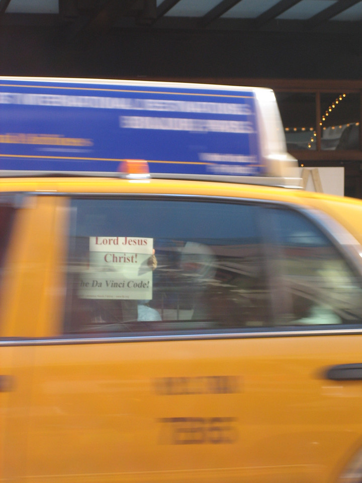 """MAY 21, 2006<br /> <br /> I love this picture.  In a cab, on the way to my DIVA bohemia storage space, I spotted some DaVinci Code protesters. When I went to take a picture of them, a cab zoomed by.  You can see the """"Lord Jesus Christ"""" sign through the window of the moving cab.  I thought it was cool."""