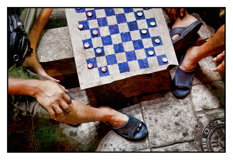 Sat 6 March - Checkers<br /> <br /> Pizza dinner on Thonglor today and spotted these two guys playing checkers by the street. Beer caps and a piece of tile is all you need...