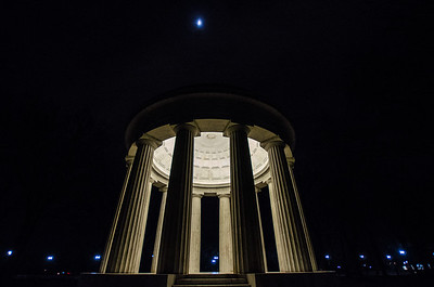 The moon hangs over the DC World War Memorial on cool winter night