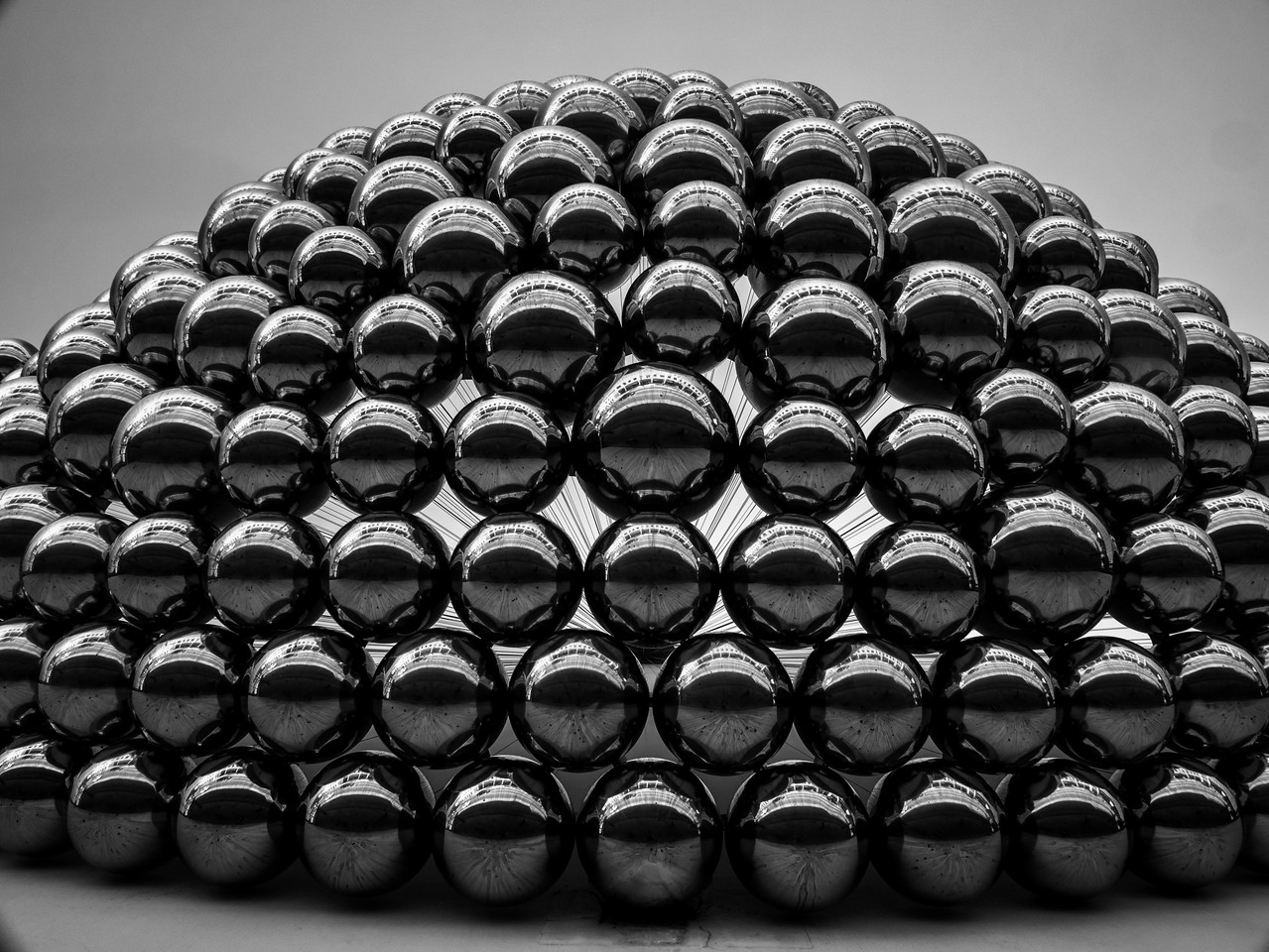 Perceiving scale can be tricky. These metals balls look smallish (like the ones swing back and forth). Since there are no clues for size it is going to hard to tell.. They are actual pretty large. At least bowling ball size and the whole installation is on the side of a parking garage In Santa Monica