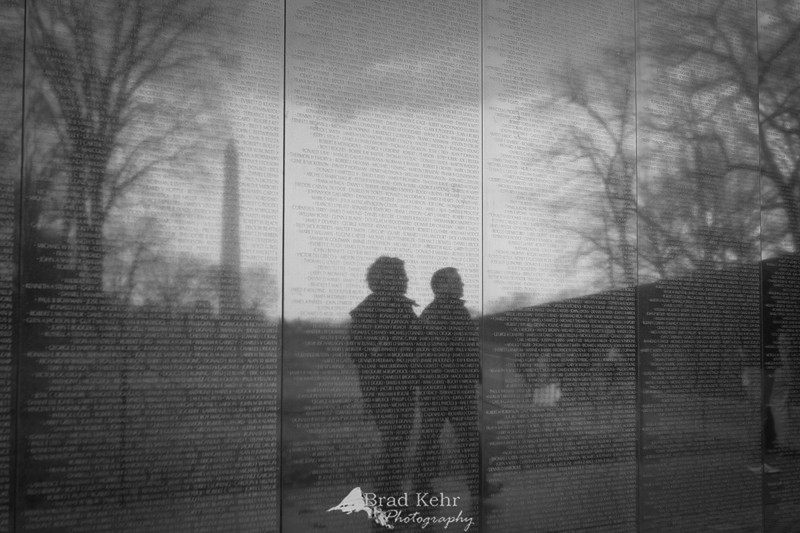 Vietnam Memorial Wall reflecting visitors and the Washington Monument - Washington, DC.