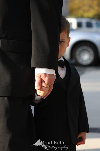 Camera Shy - The Ring Bearer Hides Behind Grandpa.