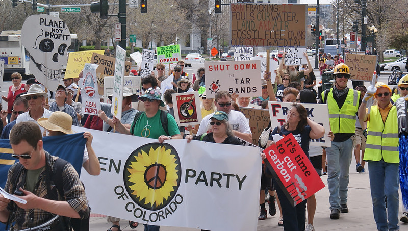 Large group of marchers with signs and banners at KXL pipeline protest, Green Party banner in front.
