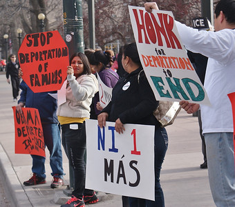 Young hispanic woman holding stop sign shaped poster against deportations, other with signs beside her.