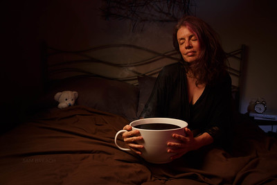 Woman luxuriates in bed with Giant Coffee Cup