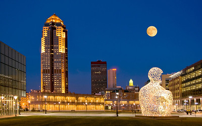This image of the downtown Des Moines Iowa skyline has the Nomad sculpture in the original location next to the Des Moines Public Library, that has the copper windows. It was taken about 20 minutes after sunset and the large full moon in the background definitely adds to the image