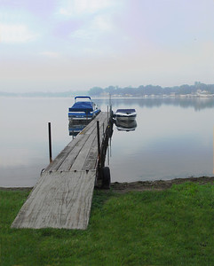 This image was taken on an early summer morning on the west shore of Lake Okoboji in the Iowa Great Lake. The light fog on a calm morning makes for a peaceful morning at the lake.