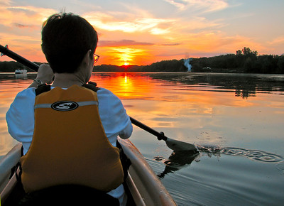 Kayaking into the sunset on Big Creek State Park in central Iowa. A very calm night, a great sunset and even a bonfire along the shore makes for a great evening on the water