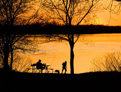 A mom, her son and their dog out fishing at Big Creek State Park. The light cloud cover makes a great golden sunset and a great silhouette of the evening.