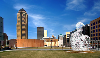 This image of downtown Des Moines Iowa skyline has the Nomad sculpture in the original location next to the Des Moines Public Library that has copper windows. It was taken in the early afternoon and to show the daylight version of the evening photo