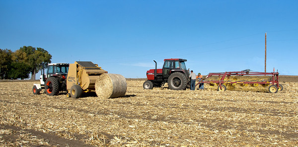 After the corn is harvest, some corn stalks are raked and then baled into large 1,500 lb. bales to be used as roughage for cattle in the winter. I cropped the top and bottom of the photo to allow more of a focus on what is taking place.