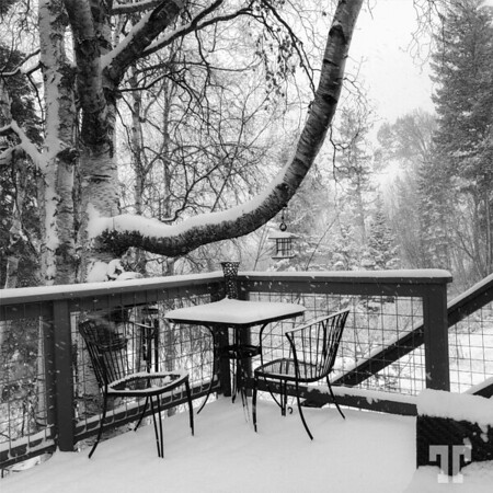 Falling snow in the Bigfork, Montana area in October, view of the balcony - black and white photo