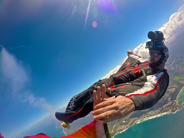Wingsuit back- flying with smoke over the Ocean in Puerto Rico