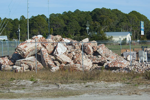 "A committee was formed to restore the lighthouse using as many of the original materials as possible.  Large chunks of the lighthouse were transported to Eastpoint on the mainland and stored for use in the restoration.  This photo, taken in January, 2007, shows the chunks of bricks.  Volunteers from all along the Gulf attended ""brick cleaning parties.""  They used jackhammers to break apart the bricks.  Then, each brick was cleaned individually to remove the old mortar."