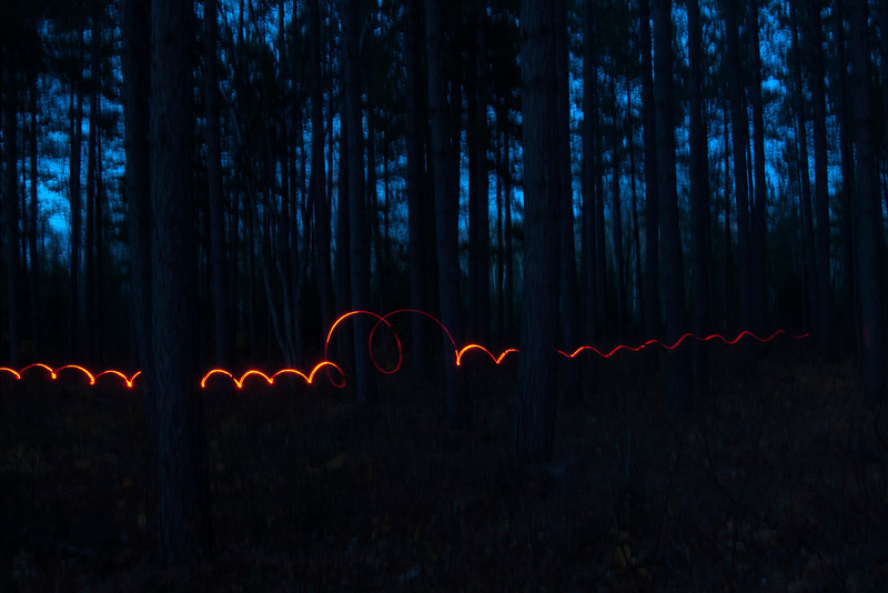 It was pretty dark already when the whole class lined up at the edge of a forest.  We set our cameras at ISO 400, f 16, and a very slow shutter speed of 15 seconds.  Our instructor, Layne Kennedy, had a red flashlight.  We pushed our shutter buttons and he walked quickly through the woods in front of us twirling the flashlight.  The result was this trail of light.  We were amazed that you can't see him at all, because he's moving quickly enough that the camera cannot record his image in the low light.