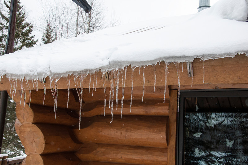Here's a view of the front of our house, taken yesterday.  Temperatures this weekend have been right around freezing, so some of the snow on the roof has started melting.  However, it's been just cold enough to form icicles.  The icicles start out hanging straight down, like they should.