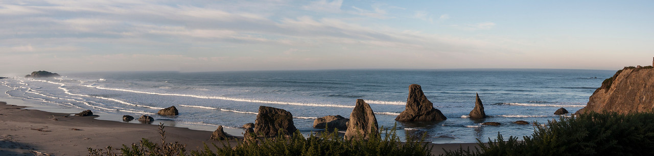 We rented a house in Bandon, Oregon, for nine days.  This was the view from the deck of the house.  It was high on a hill overlooking the Pacific Ocean.  I took five photos from left to right and stitched them together in Photoshop to get this panoramic view.  Large rocks like those in the water are found all along the coast.  Some have been given names like Elephant Rock, Face Rock, and Cat and Kittens.  The names are either based on legends or just what people think the rock looks like.